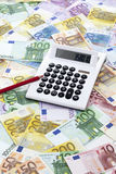 Calculator and pen on heap of euro notes Royalty Free Stock Photos
