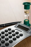 Calculator, pen and hourglass in the morning sun Royalty Free Stock Photos