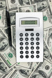 Calculator and pen lying on the million dollar. Royalty Free Stock Image
