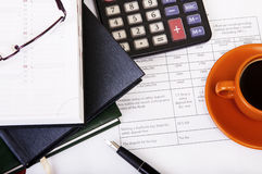 Calculator,pen, notebook and business reports. Coffee Break Royalty Free Stock Images