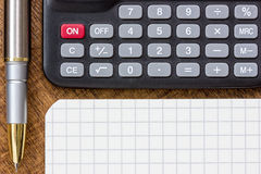 Calculator, pen and notepad on the table Royalty Free Stock Image