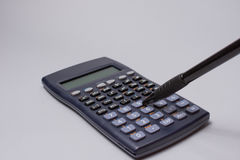 Calculator and pen on the office table on white background. Budget concept. Calculator and pen on the office table on white background Royalty Free Stock Photography