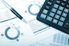 Calculator, pen over annual report. Business pen and calculator over annual report royalty free stock photography