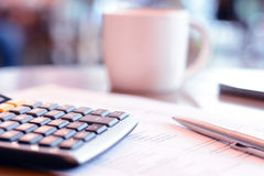 Calculator & pen over paper on the table with blur coffee cup background Royalty Free Stock Photo
