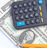 Calculator, pen and pad at dollars Stock Images