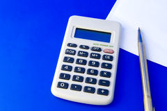 Calculator, pen and paper. Isolated on blue background Stock Photos