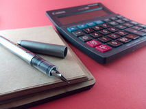 Calculator and Pen on Paper Notepad Royalty Free Stock Photography