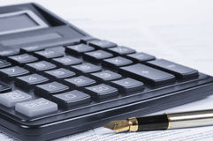 Calculator, pen, papers. Calculator and feather pen on documents Royalty Free Stock Image