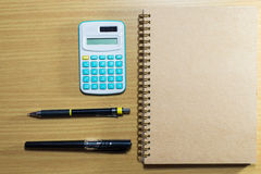 Calculator,pen,pencil and notebook on wooden table. Top view Stock Photo