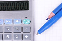 Calculator, pen and pencil on sheet of paper Royalty Free Stock Image