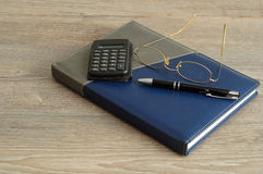 A calculator, pen and reading glasses on top of a note book. Displayed on a wooden background Stock Image