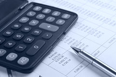 Calculator and pen on report Royalty Free Stock Photos