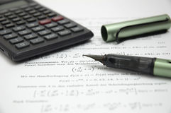 Calculator and pen on scientific paper. Calculator and open pen on scientific paper, shallow dof with focus on the tip of the pen Royalty Free Stock Images