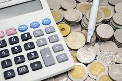 Calculator with a pen on stack of coins Royalty Free Stock Photography