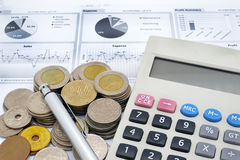 Calculator, pen and stack of coins on written graph Stock Images