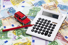 Calculator with pen and toy car on heap of euro notes Stock Photography