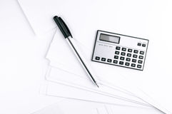Calculator and pen on white paper sheets Royalty Free Stock Images