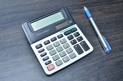 Calculator with pen on wood board background stock image