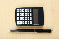 Calculator with pen on wooden background Stock Photo