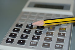 Calculator and a pencil. Science calculator with black and yellow pencil Royalty Free Stock Image