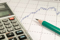 Calculator and pencil  coins on graffica the Dow Jones. Calculator and pencil and coins on graffica the Dow Jones on forex market Stock Image