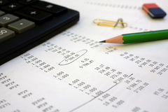 Calculator and pencil on the financial report. The calculator, pencil lay on the financial report. One number is led round Royalty Free Stock Image