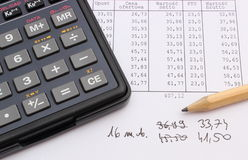 Calculator and pencil lying on spreadsheet Royalty Free Stock Images