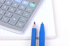Calculator, pencil and pen on paper notebook. Closed-up  on white Stock Photos