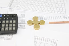 Calculator and pencil between pile of gold coins as plus Stock Images