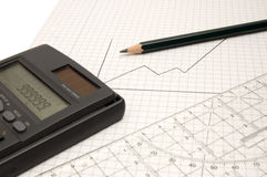 Calculator, pencil and ruler. Still life of a calculator, pencil and ruler on squared paper with drawn upward graph Royalty Free Stock Photo