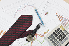 Calculator, pencil, wristwatch and necktie on graph background. Royalty Free Stock Photography