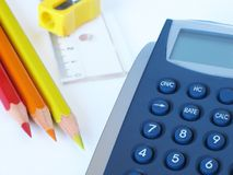 Calculator and pencils. Pocket calculator, color pencils and ruler in white background stock image
