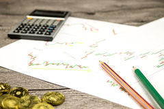Calculator,pencils and coins on graffica the Dow Jones on forex market. At grey table Royalty Free Stock Photography