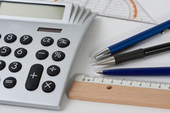 Calculator with pens and a ruler. Close-up of a calculator with pens and a ruler Stock Photos