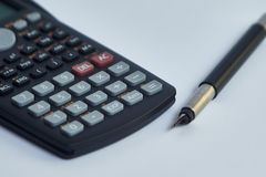 Math calculator and fountain pen lie on white paper close-up stock images