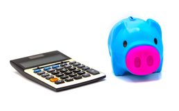 Calculator with piggy bank on white background stock image