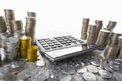 Calculator between pile of coins Royalty Free Stock Photos