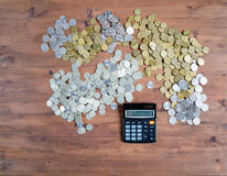 Calculator and pile of coins Stock Image