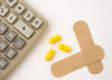 Calculator in poor health. Calculator with pills and plasters on a white background Royalty Free Stock Photos