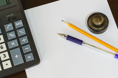 Calculator, print, pen and pencil lying on a blank sheet of paper. Stock Image