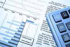 Calculator and printed financial report. Cold photo filter Royalty Free Stock Image