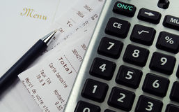 Calculator with receipts and menu. A calculator surrounded by credit card receipts and a menu Stock Photography