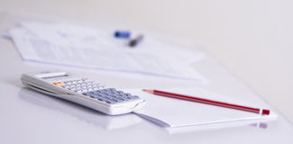 Calculator and red pencil. With paper on a business table Stock Photo