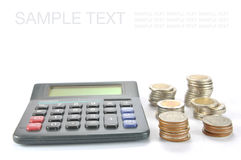 Calculator with Row of coins Stock Image