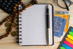 Calculator, rozentuin, muntstukken, bankbiljetten, boek, schouwspel en pen op houten achtergrond stock fotografie