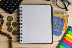Calculator, rozentuin, muntstukken, bankbiljetten, boek, schouwspel en pen op houten achtergrond stock foto's