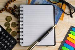 Calculator, rozentuin, muntstukken, bankbiljetten, boek, schouwspel en pen op houten achtergrond stock afbeelding