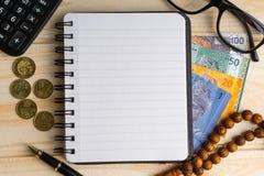 Calculator, rozentuin, muntstukken, bankbiljetten, boek, schouwspel en pen op houten achtergrond royalty-vrije stock afbeelding