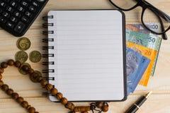 Calculator, rozentuin, muntstukken, bankbiljetten, boek, schouwspel en pen op houten achtergrond royalty-vrije stock fotografie