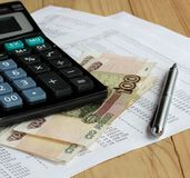 Calculator and Russian money on sheets of paper with numbers. Royalty Free Stock Images